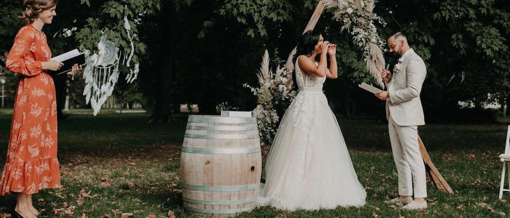Brautpaar gibt sich persönliches Eheversprechen auf Wiese vor Traubogen.