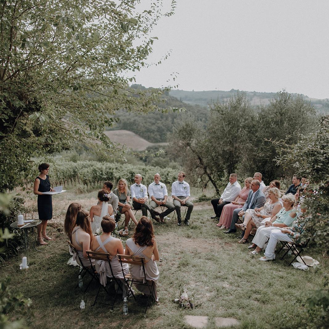 Freie Rednerin Verena führt Freie Trauzeremonie in Natur mit Brautpaar und Gästen vor Weinbergen durch.