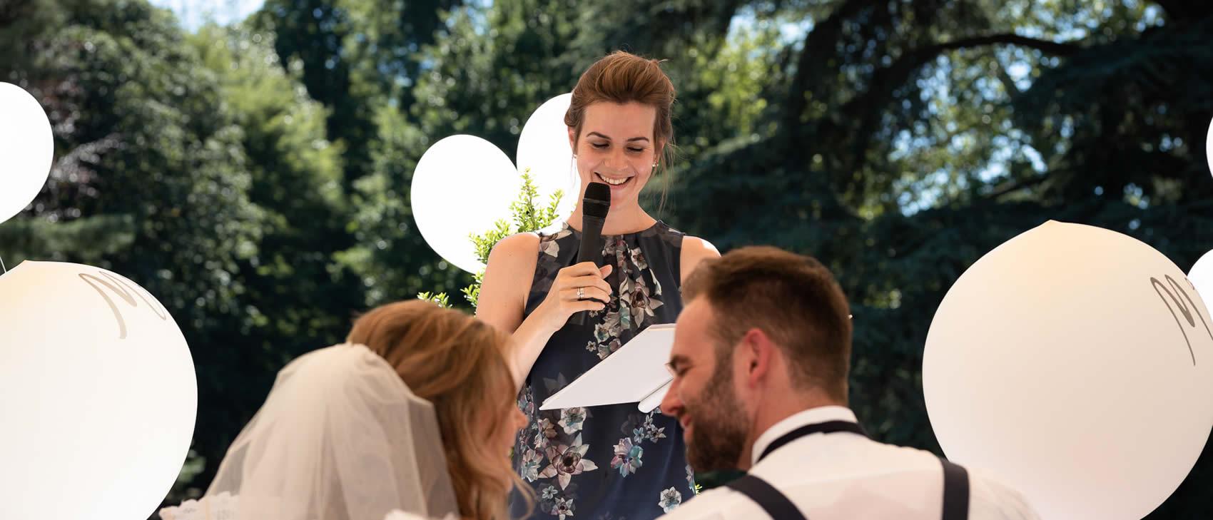 Traurednerin Verena hält Traurede vor lachendem Brautpaar.