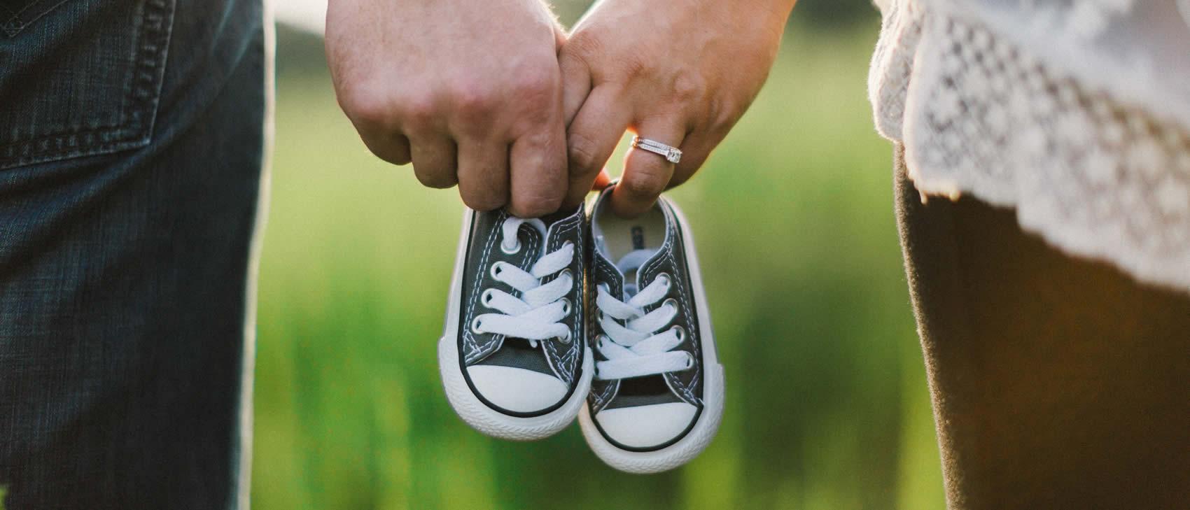 Brautpaar mit Babyschuhen in den Händen.