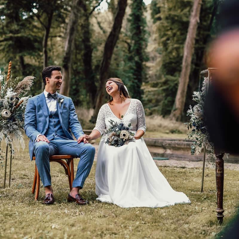 Brautpaar lacht während Freier Trauung mit Traurednerin Verena.
