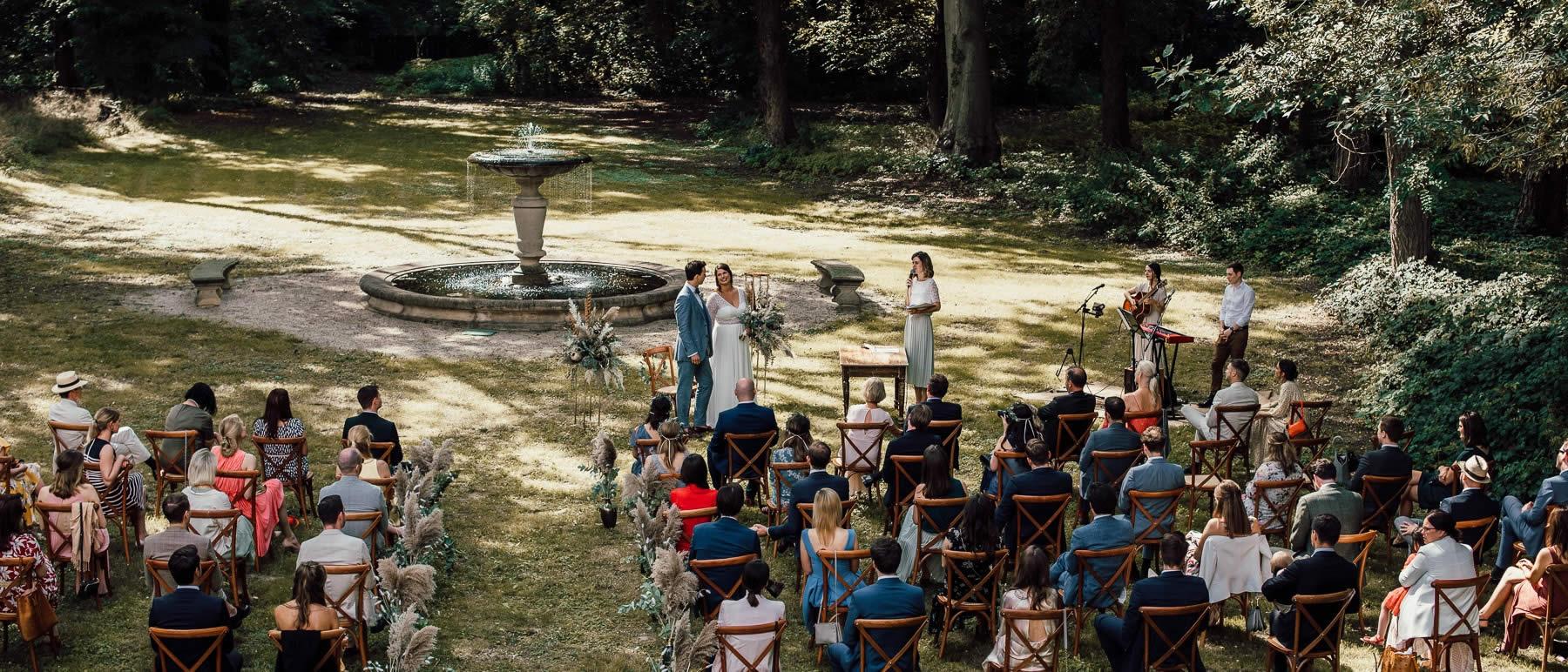Brautpaar und Traurednerin Verena während Freier Trauung im Schlosspark.