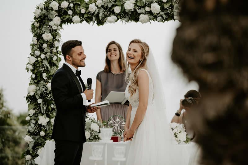 Traurednerin Verena traut Brautpaar humorvoll unter Traubogen.